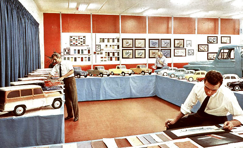 Man seated in a showroom with miniature model jeeps seated and examining an illustration