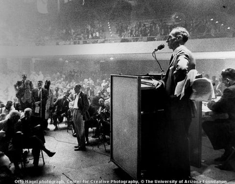 Black and white photo Harry Bridges standing behind a lectern in a crowded, smoke-filled auditorium