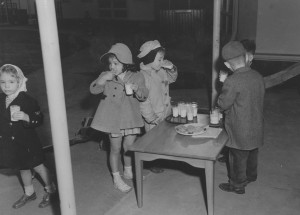 Black and white image from the 1940's of young boys and girls having a snack.