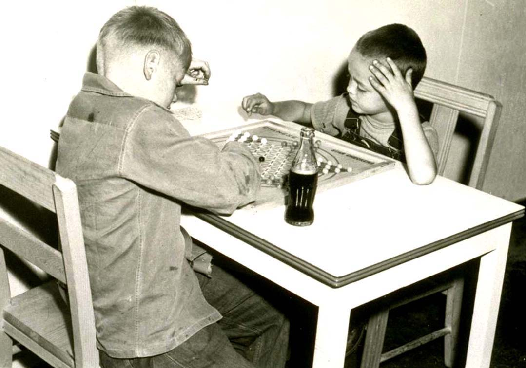 Black and white photo  of two small boys seated at a table and playing Chinese checkers
