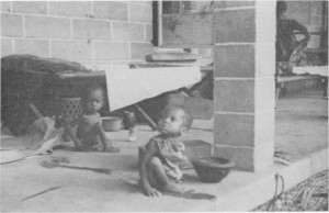 Two young Nigerian childrean sit in front of wood and canvas cots from a package disaster hospital in 1970.
