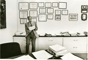 Sam Sapin in his office, sitting on a filing cabinet with numerous framed certificates on the wall.