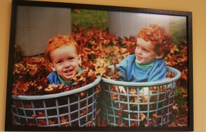 Two smiling red-headed boys in the autumn red leaves.