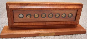 Wooden display case displaying gold, round service pins