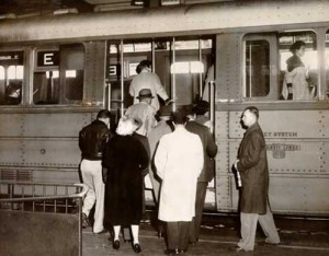Historical photo of people getting on a train. The Key System ran on the lower deck of Bay Bridge from Oakland to San Francisco until 1958 when the train service was discontinued.