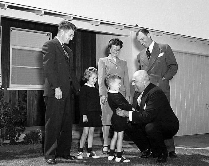 Henry J. Kaiser greets the George family at the Kaiser Community Homes