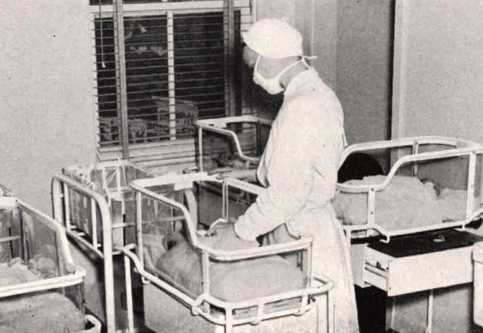 nurse attending to baby in nursery