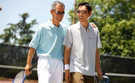 Older asian man with arm over adult son talking on a tennis court