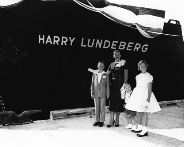 "A 1958 image of a woman and 3 children in front of a ship's hull with the name ""Harry Lundenberg"""