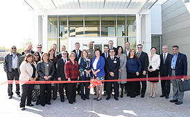 group of people behind a red ribbon for ribbon cutting ceremony at the new Victorville KP office