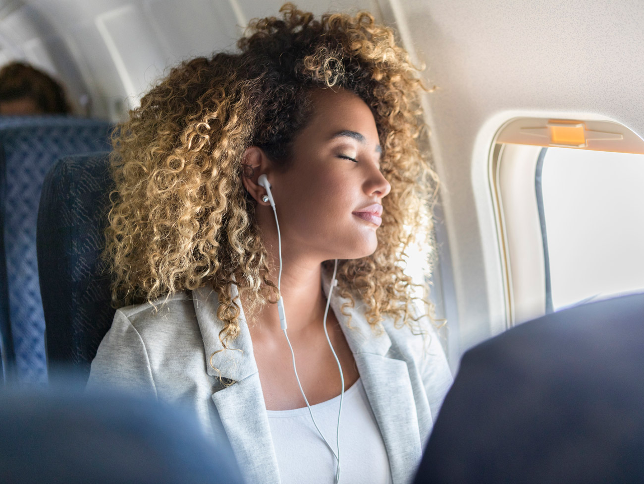 Relaxed young woman listening to her earbuds while on an airplane.