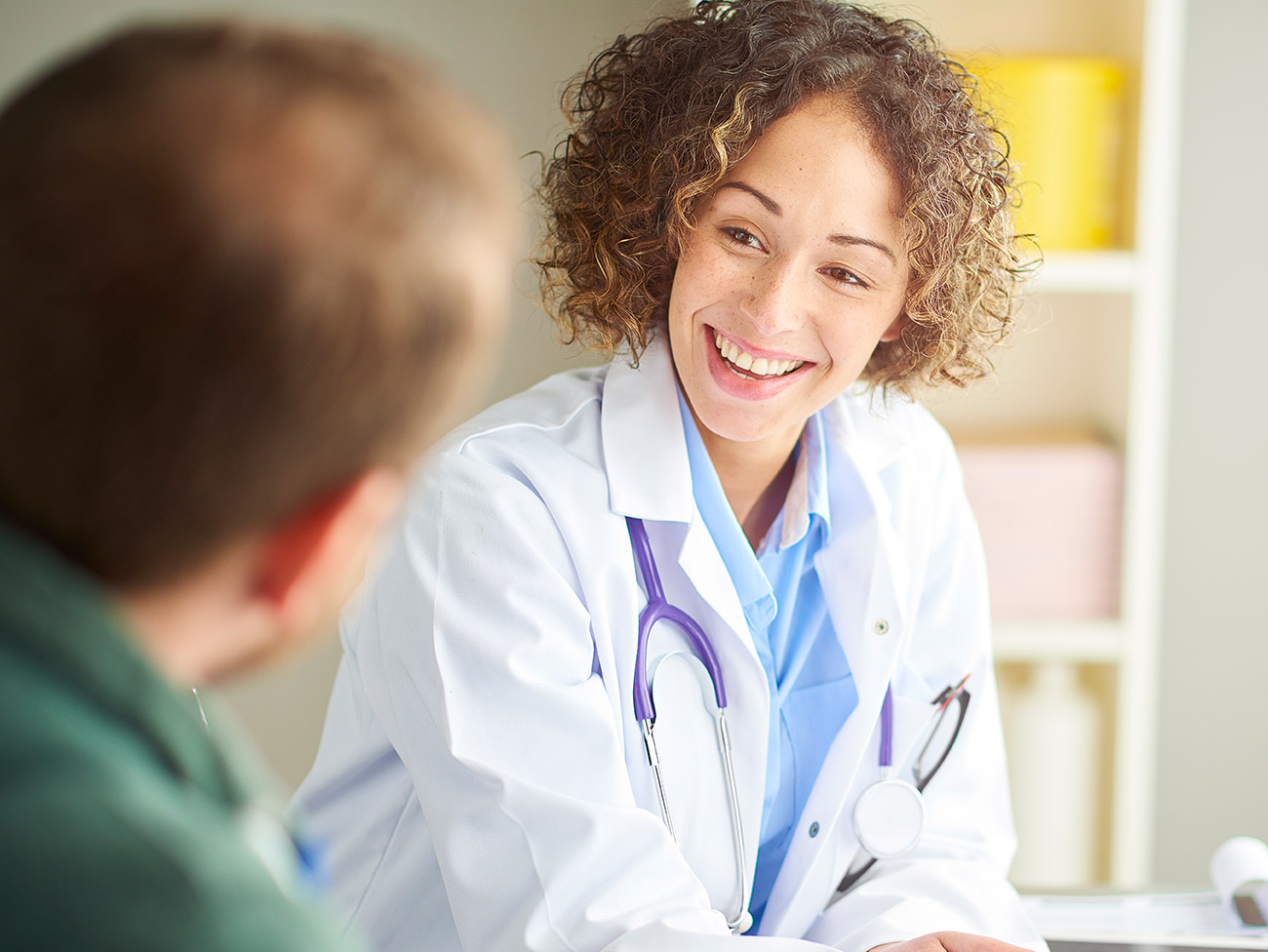 Male patient listening intently while female doctor reviews chart