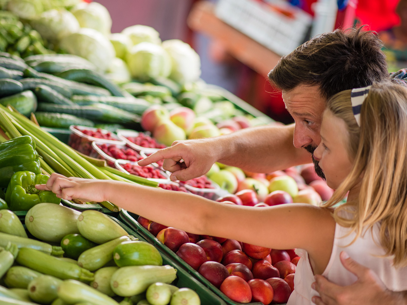 Father and daughter shopping for fresh vegetables at a farmers market