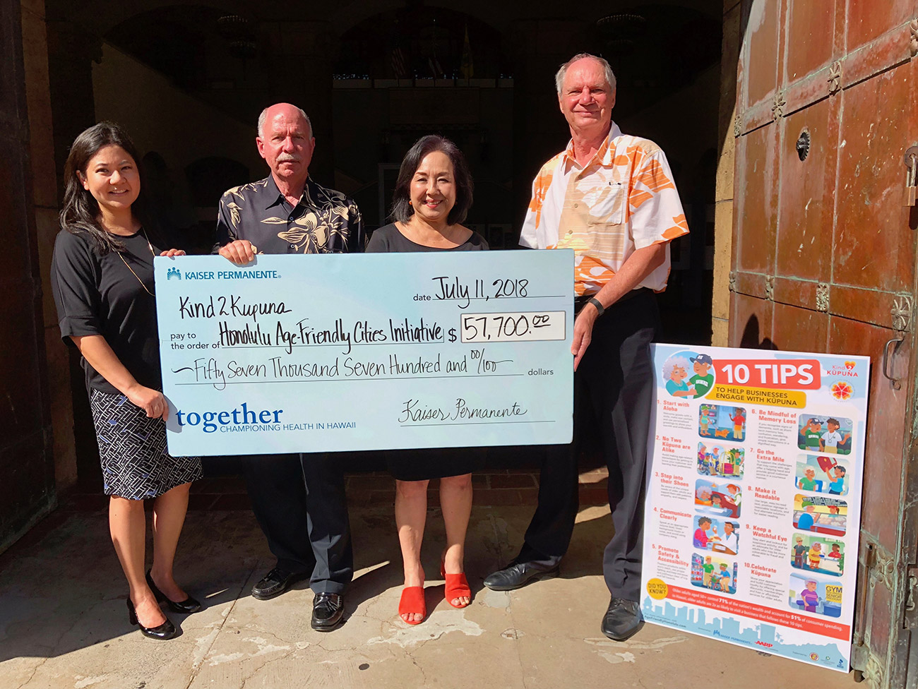 Christy Nishita, Ph.D., Terry Muldoon, Georgette Deemer, Frank Streed holding a giant replica bank check.