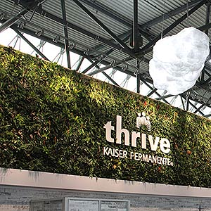 Living wall of plants with a sign that reads 'thrive - Kaiser Permanente'