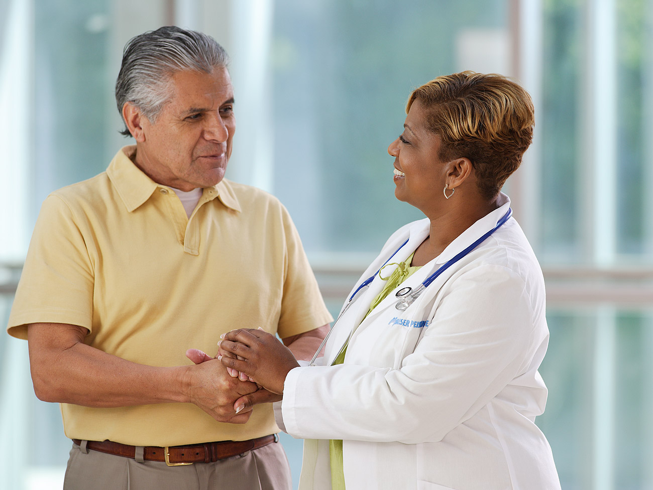 Older Hispanic man talking to his African American female doctor