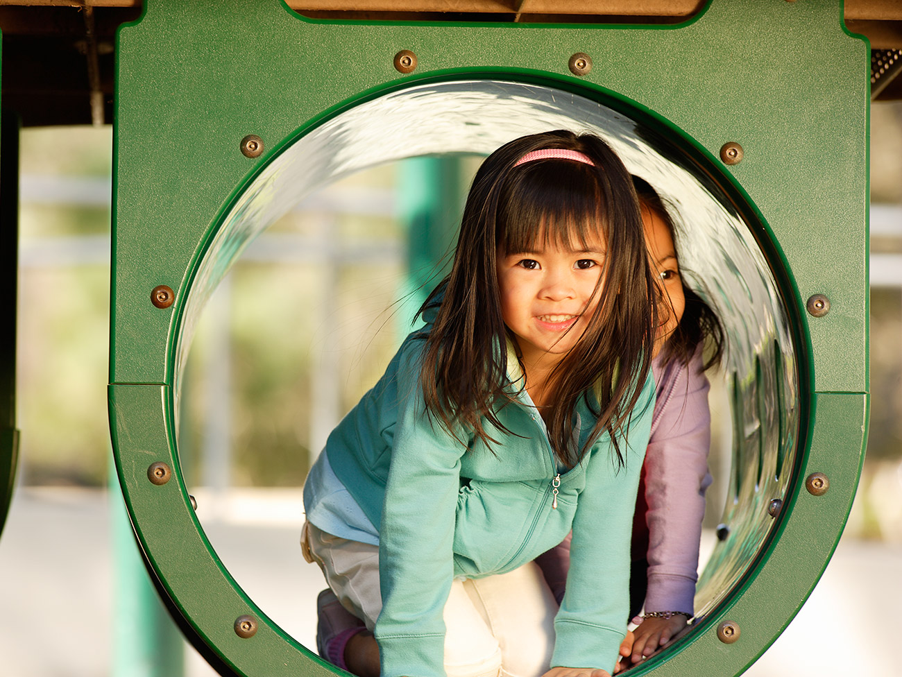 Grammar school aged Asian girl playing on a jungle gym in a park.