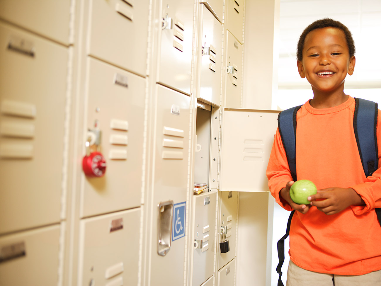 Smiling boy holding an apple next to school lockers.