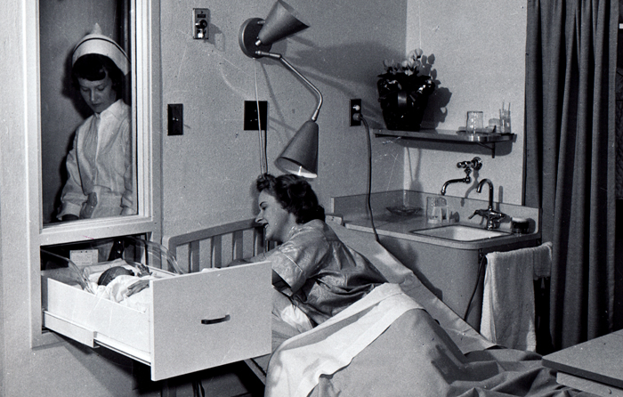 Woman lying in bed tending to baby in wall-mounted sliding drawer as Kaiser Foundation Medical Center nurse looks on