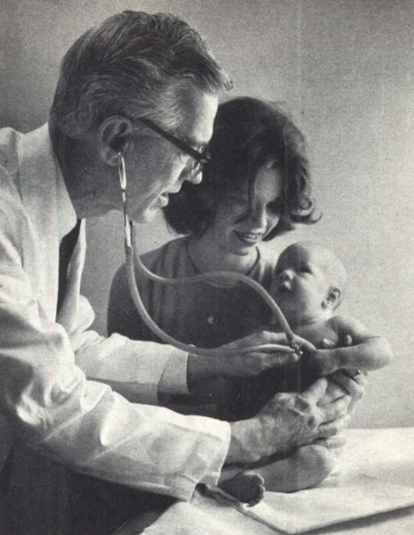 1963 image of a doctor examining an infant who is in his mother's arms.