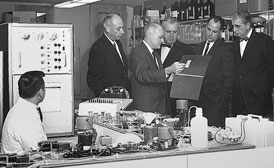 Black and white photo of a computer lab with a bunch of men in suits.
