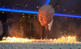 At night, an older man is lit from below by 100 candles on a cake and he is blowing them out.
