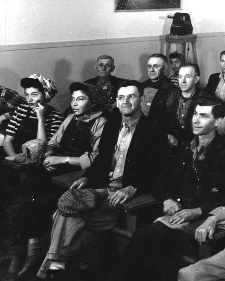 Group of men and women dressed in working clothes seated in rows facing toward the front of room