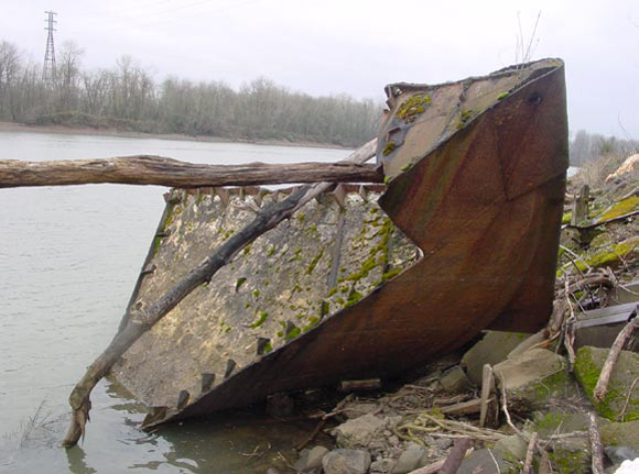 A rusted, Scrapped Liberty ship fore peak on the shore next to a river.