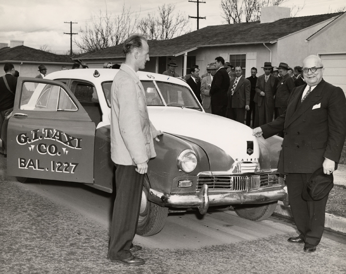 Black and white photo of Henry J. Kaiser presenting a Kaiser-Frazer car to the G.I. Taxi company