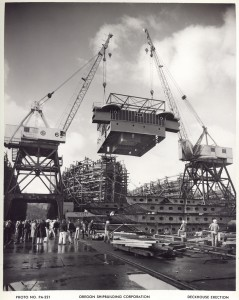 Two whirley cranes lifting deck superstructure, Kaiser Oregon shipyards, 1942.