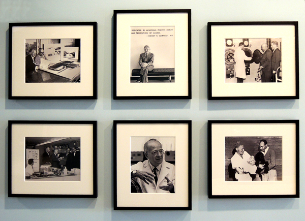Six framed black and white photographs on a wall