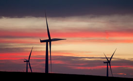 Beautiful sunset sky with clouds that are orange and yellow and red and purple behind silhouettes of three huge wind turbines from the Altamont Pass area of northern California
