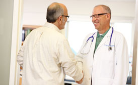 Older middle-aged male physician shaking hands with older middled-aged man