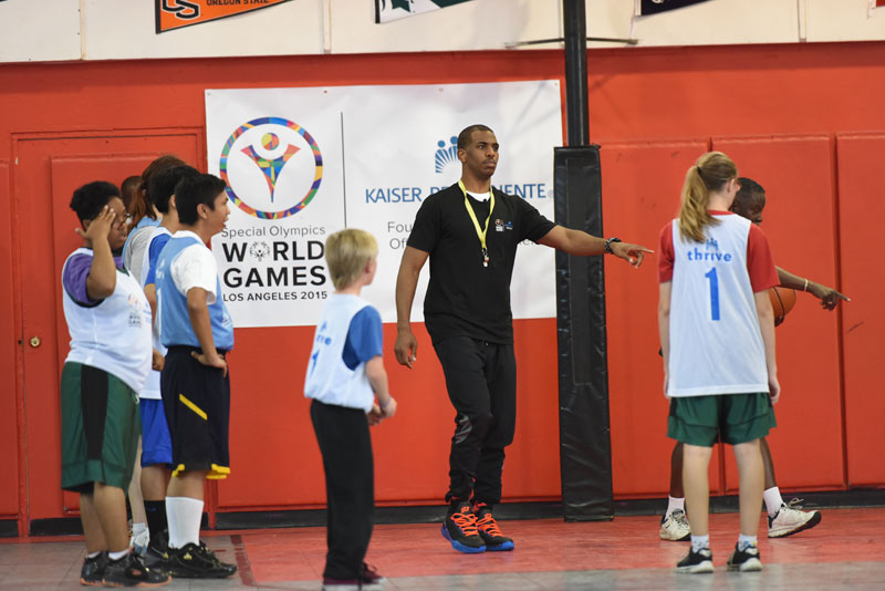 Chris Paul gesturing to kids to get them into position on an indoor basketball court