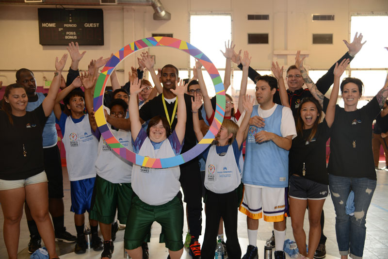 Excited kids posing with Chris Paul and the Special Olympics ring