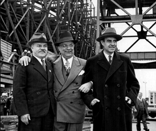 1945 black and white image of 3 smiling business men in suits at a shipyard.