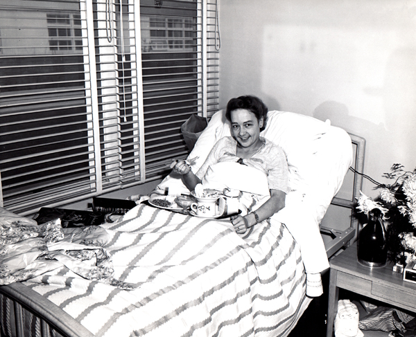 1943 image of  smiling woman in a hospital bed with a meal tray on her lap.