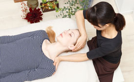 One woman is lying down on a massage table, face up. The chiropractior is seated on a stool and positioned at her head. She is adjusting the woman's head and neck.
