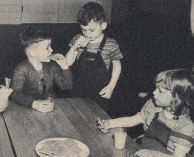 1943 black and white image of 3 children eating a snack at a table.