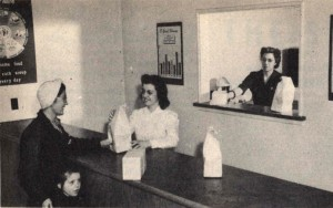 1944 historical photo of parent picking up prepared meal at Kaiser child care center.