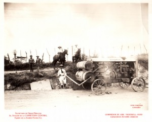 1927 photo of a man wiht a horse and cart loaded with an air compressor.