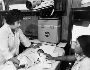 Historical black and white photograph inside a mobile health unit with medical personnel, neonatal patient and mother