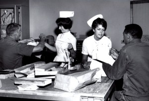1969 black and white photo of two female nurses in uniform talking to two male patients.