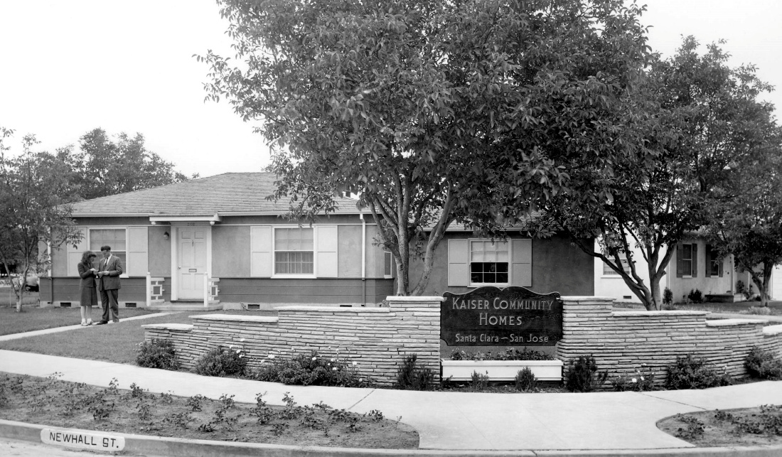 Historical image of a house in a subdivision. A man and woman are standing in the walkway.