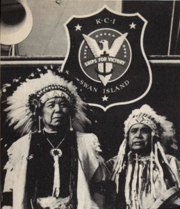 A historical black and white photo of two Native American chiefs in traditional garb.