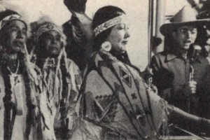 A historical black and white photo of a Native American princess in traditional garb.