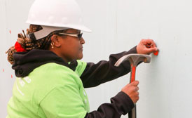 Woman hammering a plastic tab onto an a wall