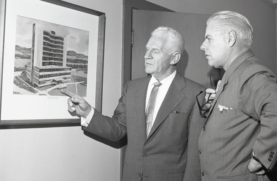 Dr. Sidney Garfield and architect Clarence Mayhew looking at illustration of planned Panorama City hospital, circa 1965