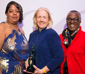 three women accepting an award from WRMSDC for Corporation of the Year