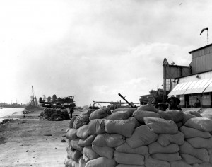 Sandbagged .30 caliber machine gun emplacement with gun crew on alert, at the seaplane base near Ford Island's southern tip, soon after the Japanese attack. Note wind sock atop hangar at right, PBY patrol plane warming up by the corner of the hangar, another PBY in the center distance, and three SOC floatplanes at left with the beached battleship Nevada (BB-36) beyond. Sandbags are marked Permanente. Official U.S. Navy Photograph, now in the collections of the National Archives.